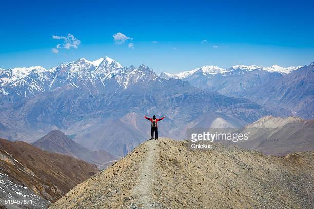 Man hiker with arms raised Annapurna trek, Nepal