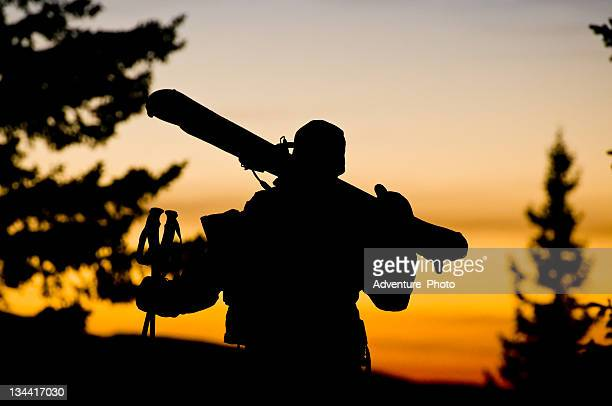 Man Hikes Into Sunset with Skis Over Shoulder