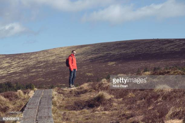 Man hikes on trail lined with railway sleepers
