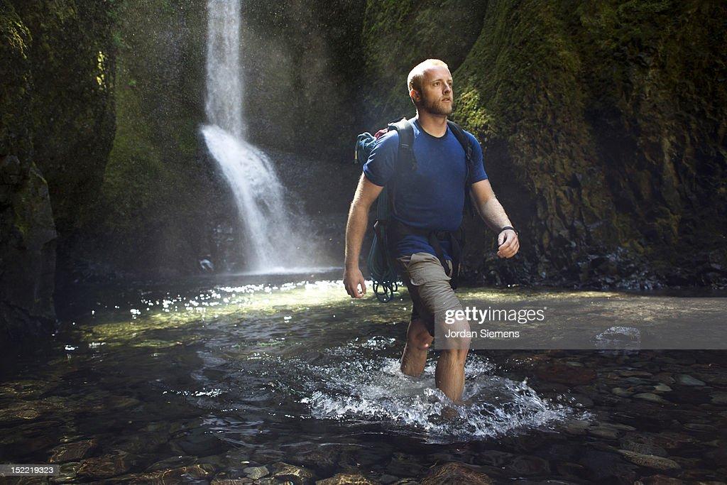 A man hiking a narrow canyon. : Stock Photo