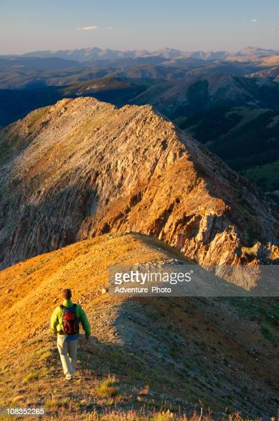 Man Hiking at Sunset along Rugged Mountain Ridge