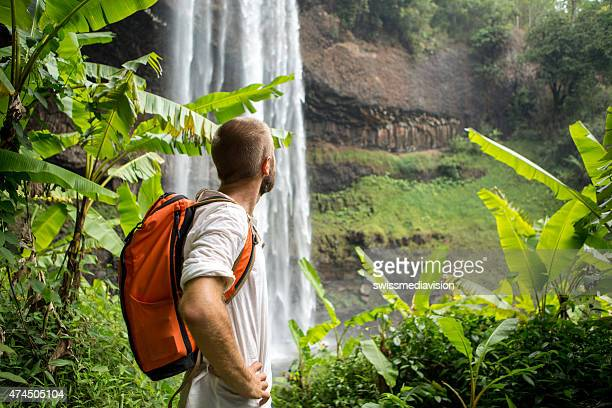 Man hiking in jungle looks at waterfall