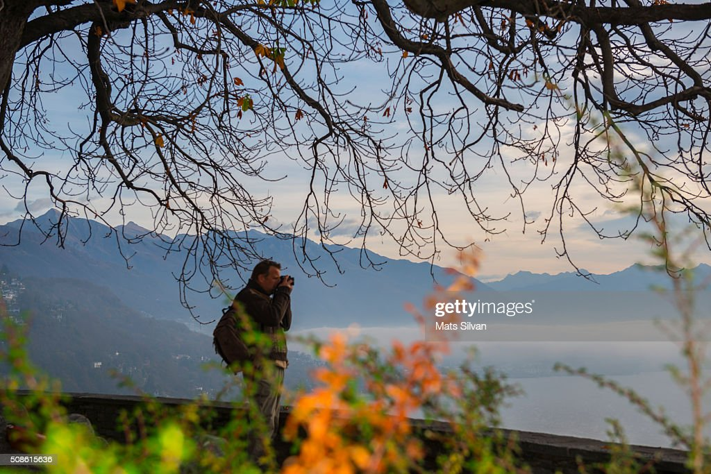 Man hiking in the nature and using a camera : Stock Photo
