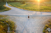 Man with backpack hiking on crossroads at sunset somewhere in European countryside. High angle view. Photo is taken with dslr camera and wide angle lens at the end of hot,summer day.