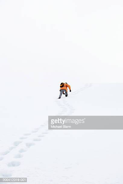 Man hiking up snow covered mountain, rear view, low angle view