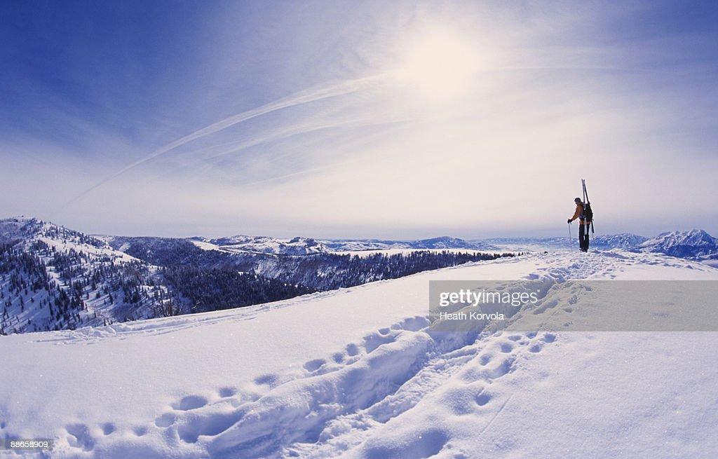 Man hiking with skis through snow in mountains. : Stock Photo
