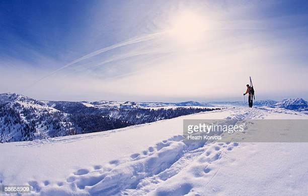 Man hiking with skis through snow in mountains.