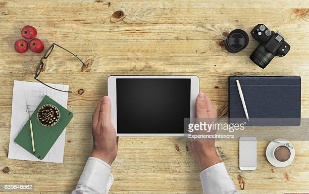 Man hipster holding tablet knolling overhead view