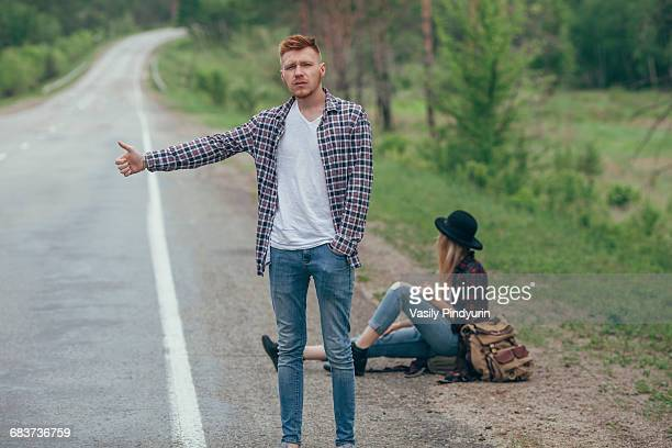 Man hitchhiking while woman sitting on roadside