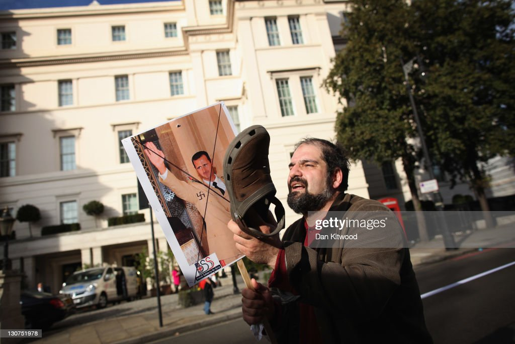 A man hits an image of Syrian President Bashar al-Assad with a shoe as Syrian protesters make their way towards the Syrian Embassy on October 29, 2011 in London, England. Amnesty International activists and Syrians living in the UK are to hold a 'No More Blood - No More Fear' rally outside the Syrian embassy to call for an end to the government crackdown in Syria, which has killed at least 3,000 people.
