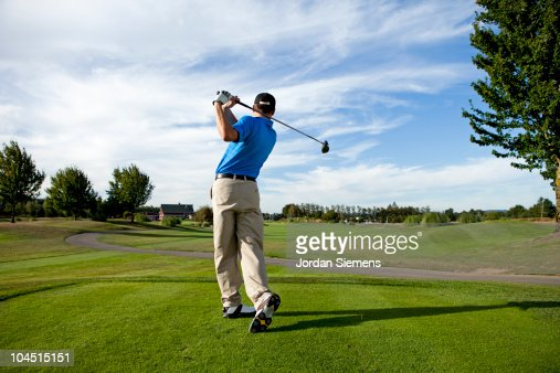 Man hitting a ball on the golf course.