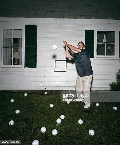 Man hitting baseballs in rain