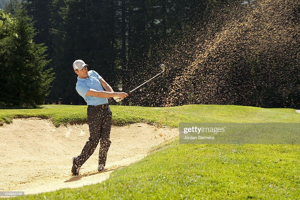 A man hitting out of a sand trap.