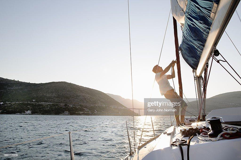 Man hoisting sail, backlit