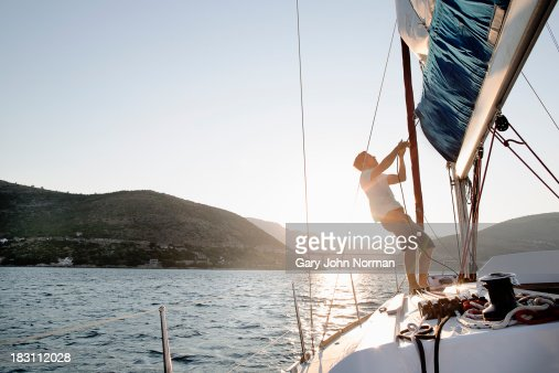 Man hoisting sail, backlit