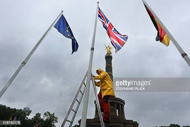 A man hoists the national flag of Britain flanked by the European and German flag in front of the Victory Column in Berlin on June 23 2015 British...