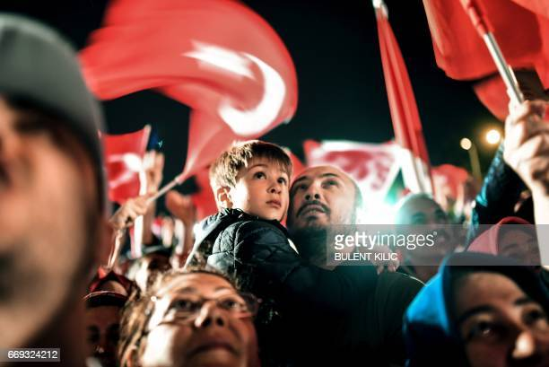 A man hold a child as they came to celebrate and greet Turkish president during a speech at the conservative Justice and Development Party...