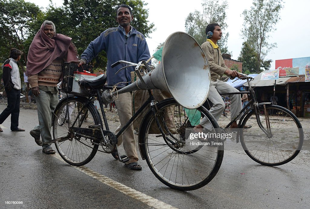 A man hold a loudspeaker on his bicycle to welcome Rahul Gandhi outside Fursatganj Airport, on February 5, 2013 in Amethi, India. Rahul's visit to his parliamentary constituency of Amethi for the first time as Congress vice president has been postponed due to inclement weather.