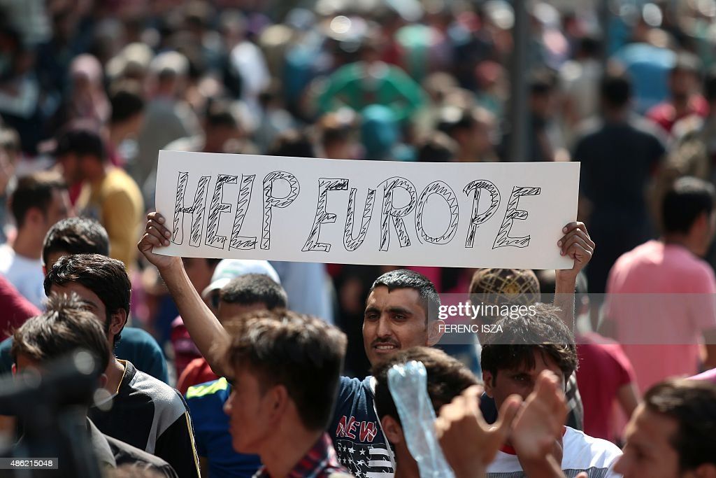 A man hold a placard reading 'Help Europe' as Syrian and Afgan refugees attend a protest rally to demand to travel to Germany on September 2, 2015 outside the Keleti (East) railway station in Budapest. Hungarian authorities face mounting anger from thousands of migrants who are unable to board trains to western European countries after the main Budapest station was closed. ISZA