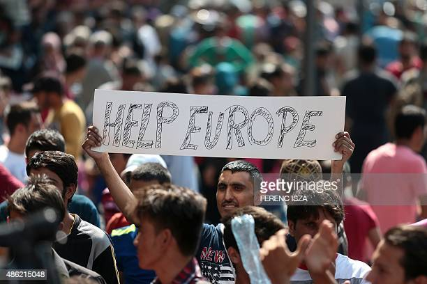A man hold a placard reading 'Help Europe' as Syrian and Afgan refugees attend a protest rally to demand to travel to Germany on September 2 2015...