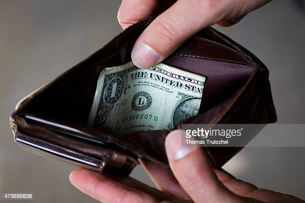 A man hold a wallet filled with a One Dollar bill on June 03 in Berlin Germany