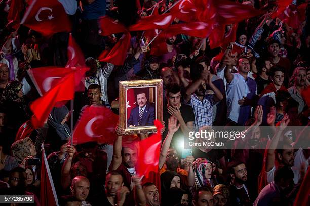 A man hold up a portrait of Turkish President Recep Tayyip Erdogan while attending a rally in Kizilay Square on July 18 2016 in Ankara Turkey Clean...