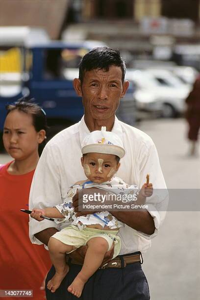 A man holding a baby with Thanakha Myanmar