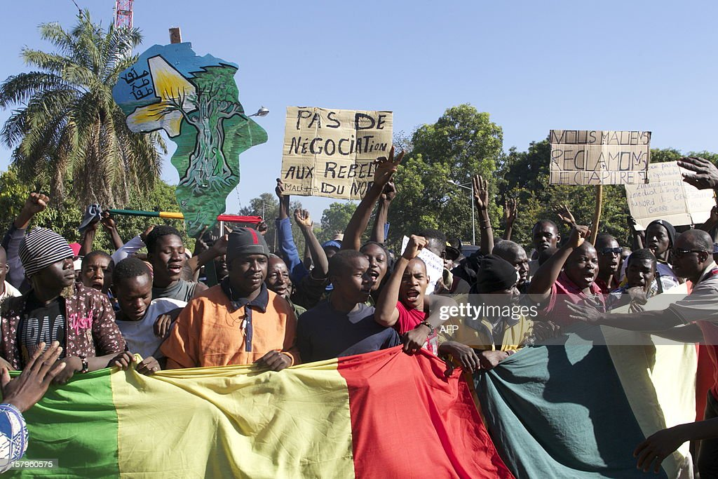 A man holding a banner that reads 'No negotiation with rebels' joins thousands of others in Bamako on December 8, 2012 in a demonsration called by several Malian political parties to support the Malian amry and demand a United Nations (UN) Security Council resolution approving the deployement of an international force in the country's north, controlled for eight months by Islamist armed groups. Facing the international community's equivocation on the matter, impatience rises in Mali's people, who say they are ready to go to war to take their 'own destiny in hand'. AFP PHOTO / HABIBOU KOUYATE