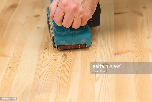 Man holding a belt sander on pine floor or table sanding surface