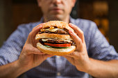 Caucasian man holding a big hamburger