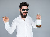 Work hard play hard. Handsome young man in sunglasses and white shirt holding a bottle of whiskey and cigar and shouting while standing against grey background