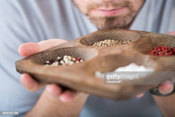 Man holding a bowl and smelling spices