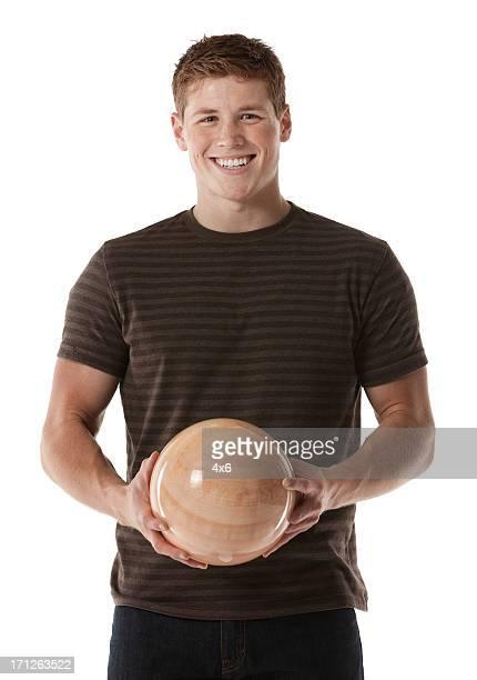 Homem segurando uma Bola de bowling