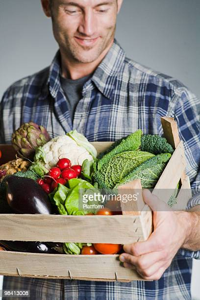 Man holding a box of vegetables.