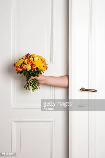 A man holding a bunch of flowers inside a door