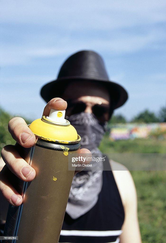 A man holding a can of spray paint