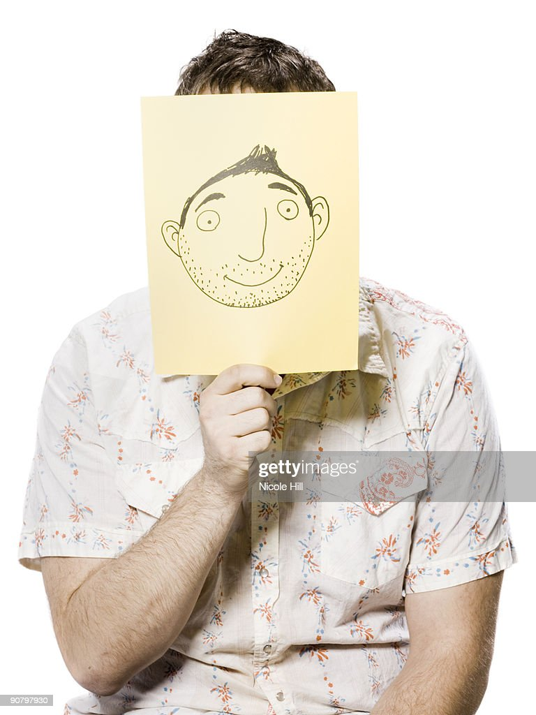 man holding a cartoon face drawing in front of his own face : Stock Photo