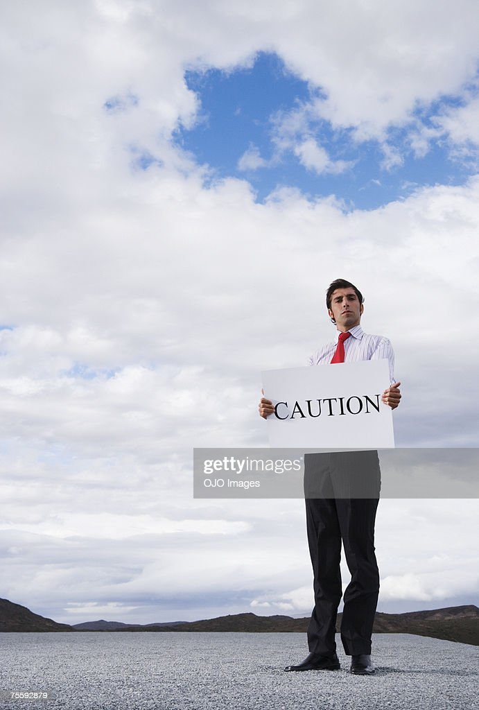 Man holding a caution placard : Stock Photo