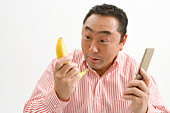 Man holding a cell phone and banana
