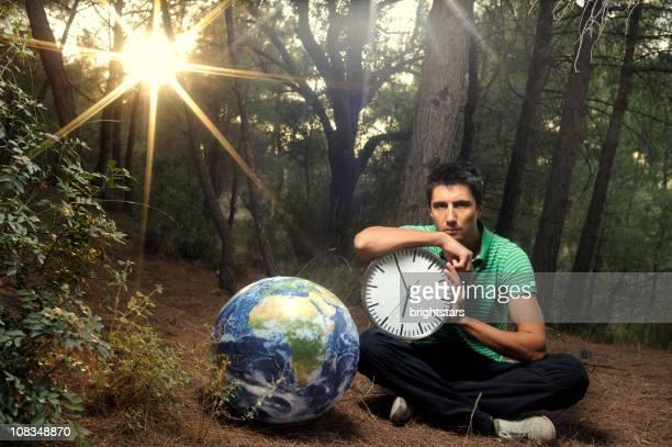 Mann hält eine Uhr in der Nähe der Erde ball