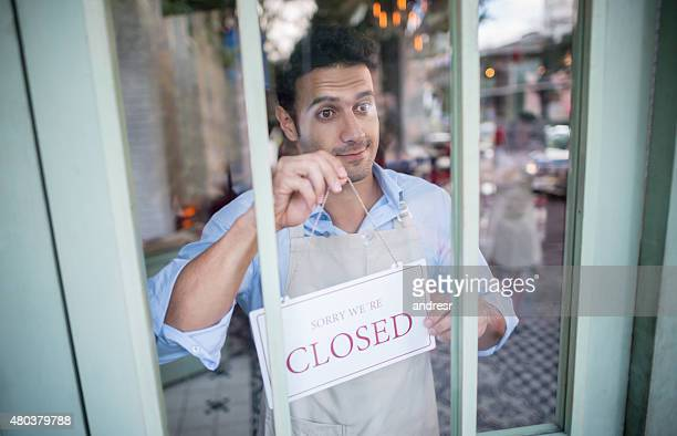 Man holding a closed sign outfront of his business