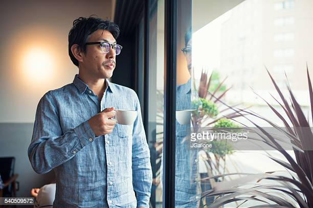 Man holding a coffee cup looking through window