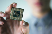 Man holding a micro computer chip, CPU from desktop computer.