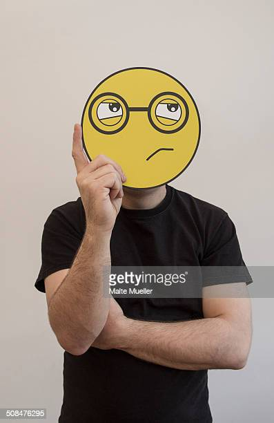 Man holding a confused emoticon face in front of his face