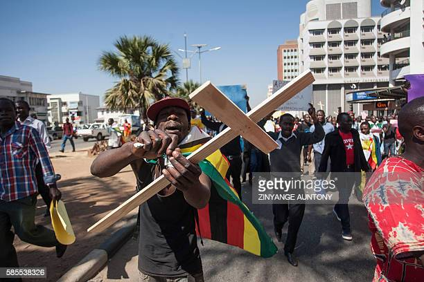 A man holding a cross tears a worthless $1000 note bearers' cheque during a protest against government plans to introduce bond notes a local token...
