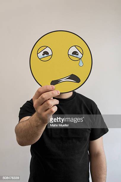 Man holding a crying emoticon face in front of his face