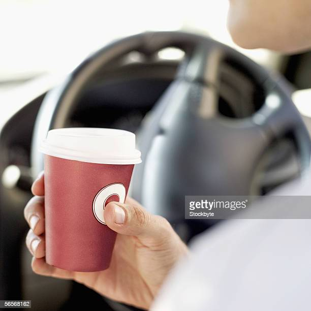 man holding a cup in a car