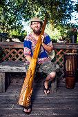 Man Holding a Didgeridoo