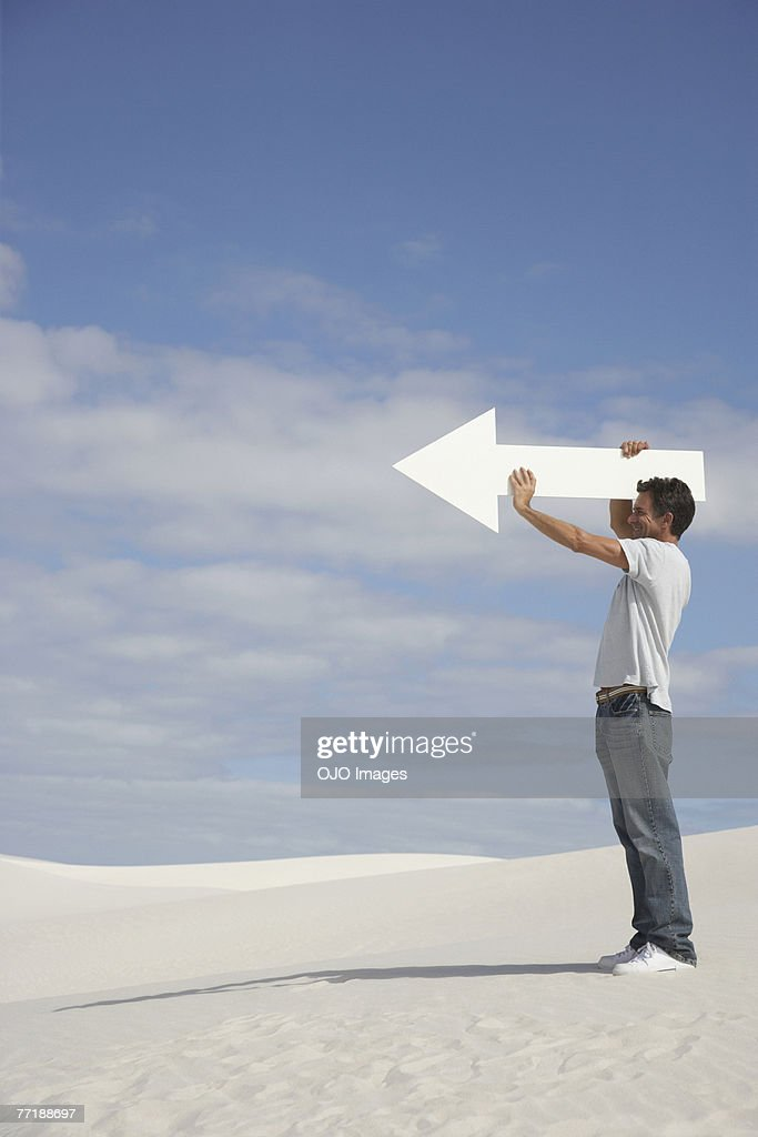 A man holding a directional arrow : Stock Photo