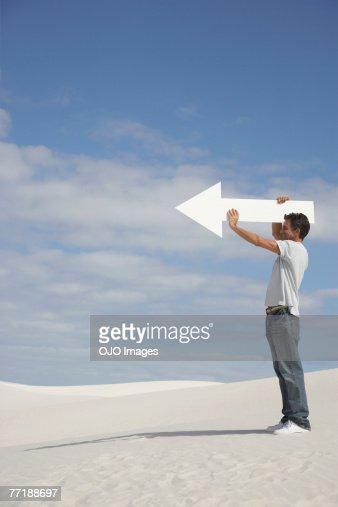 A man holding a directional arrow : Stock Photo